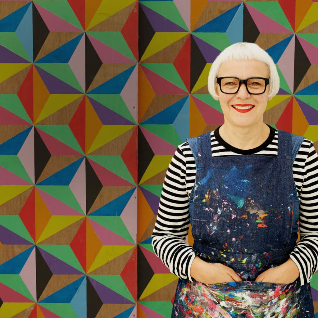 Image of artist and designer Morag Myerscough in front of her designs for method cleaning products