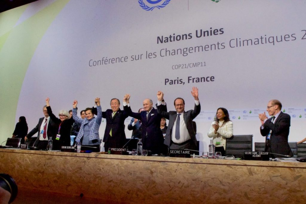 World leaders hold hands to celebrate the Paris climate agreement
