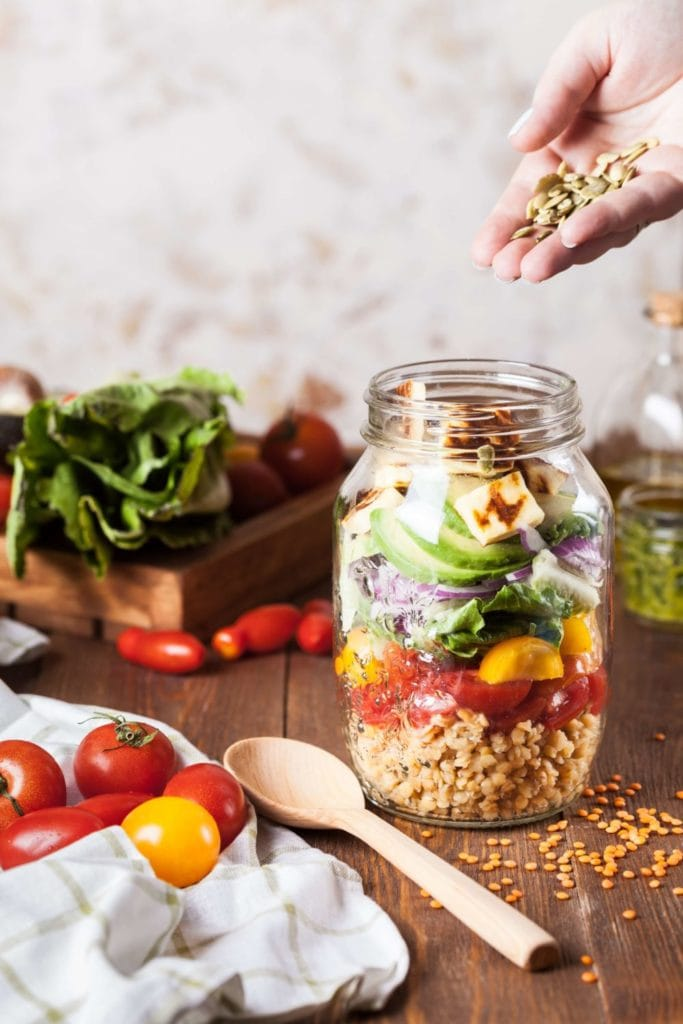 Image of woman's hand pouring healthy food into jar