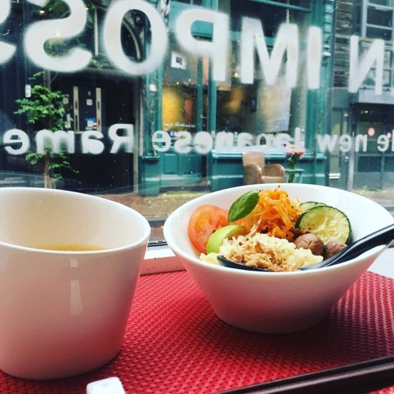 A bowl of Ramen on bench next to the front window of the Men Impossible Restaurant