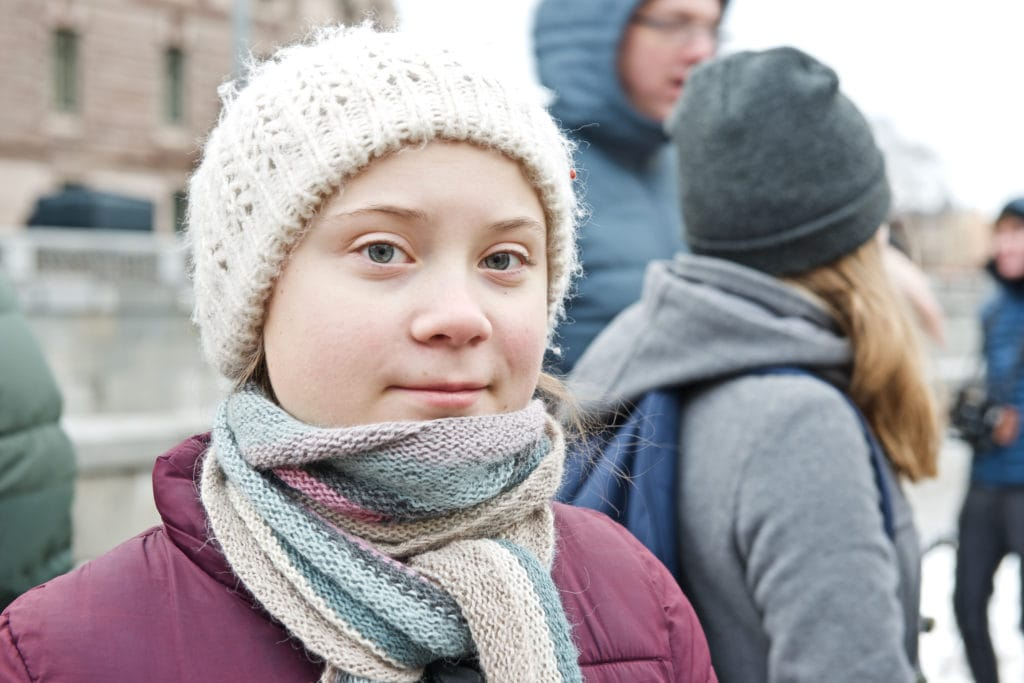 Image of Greta Thunberg, wearing a white wooly hat and looking directly at the camera