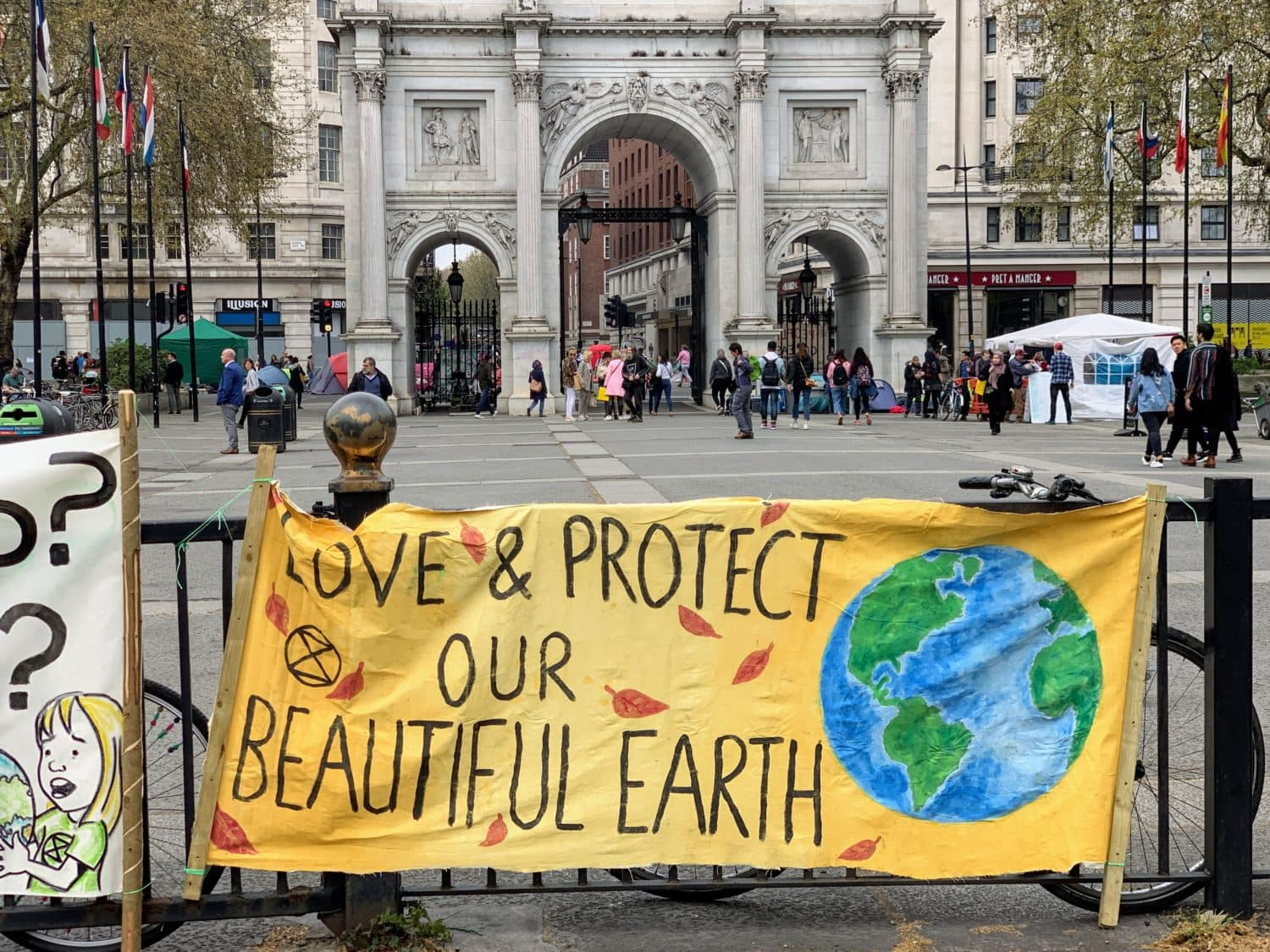 Banner saying Love and Protect our beautiful earth in front of Marble Arch