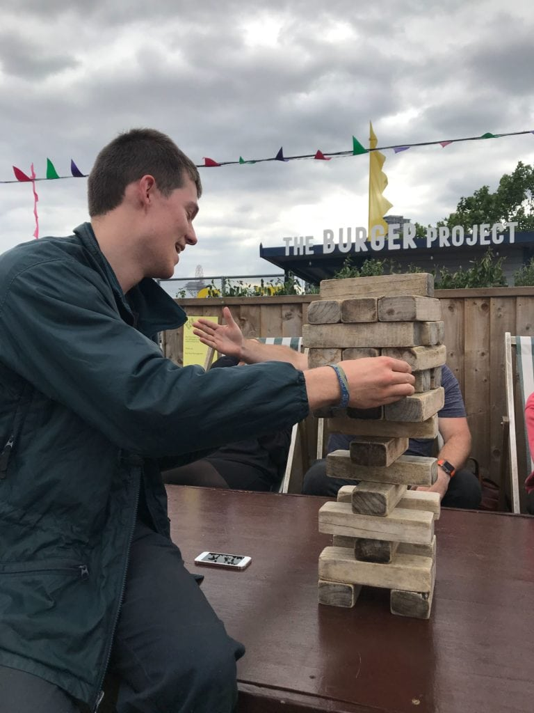 Jerome playing jenga on a rooftop - on our team day