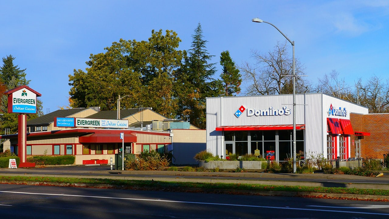 A Dominos pizza store next to a road in the USA