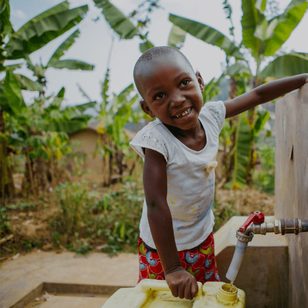 Child smiling at the camera , in front of a water tap which she is using to fill a yellow container