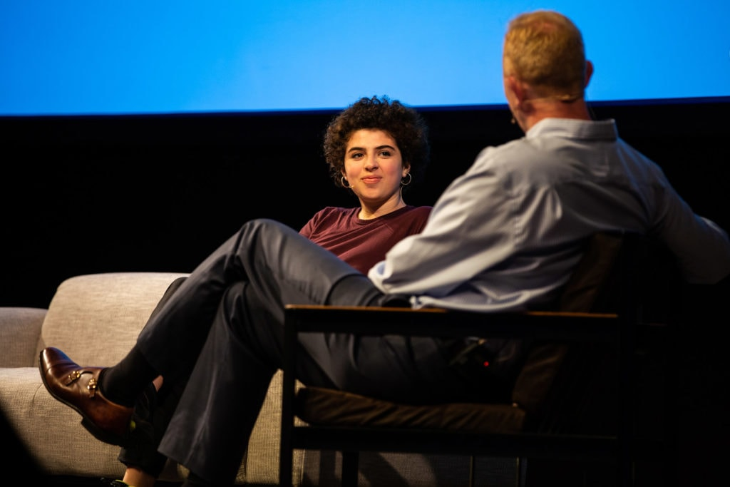 Andrew Medhurst and Noga Levy-Rapoport sit facing each other, in conversation on the stage