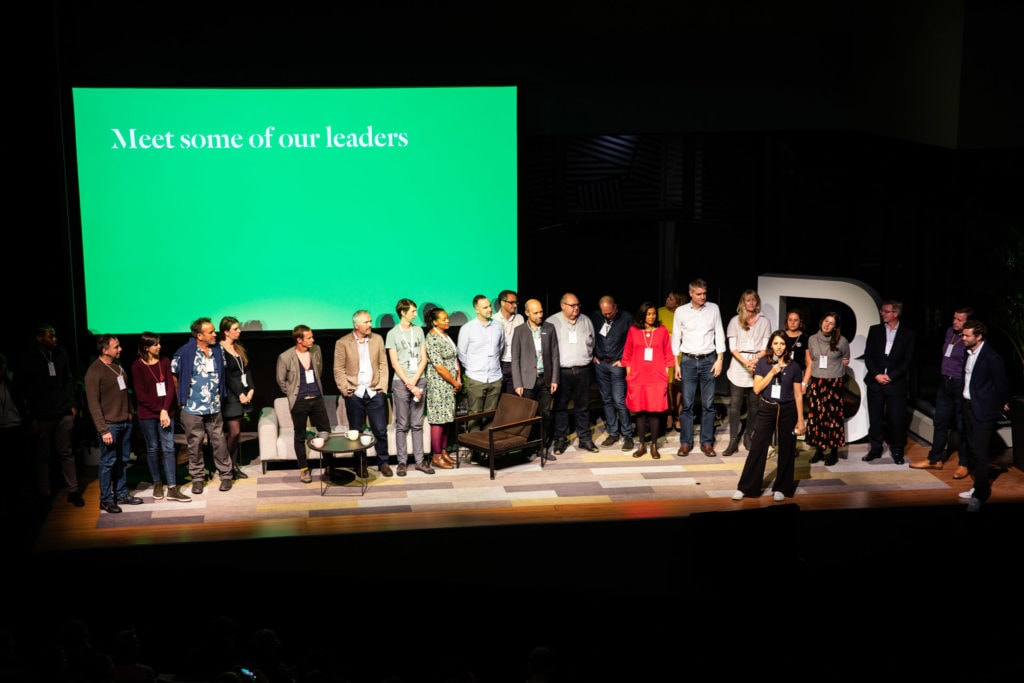 A group of people from B Corporation stand in front of a green screen displaying the text 'Meet some of our Leaders'