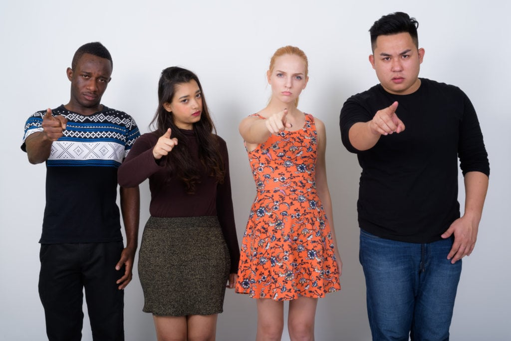 Diverse group of young people pointing in your face